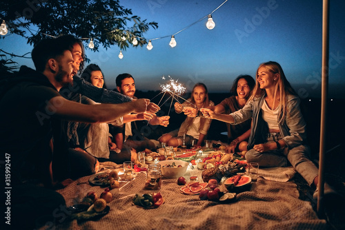 Obraz Happy friends having fun with fire sparkles. Young people millennials camping at picnic after sunset. - fototapety do salonu