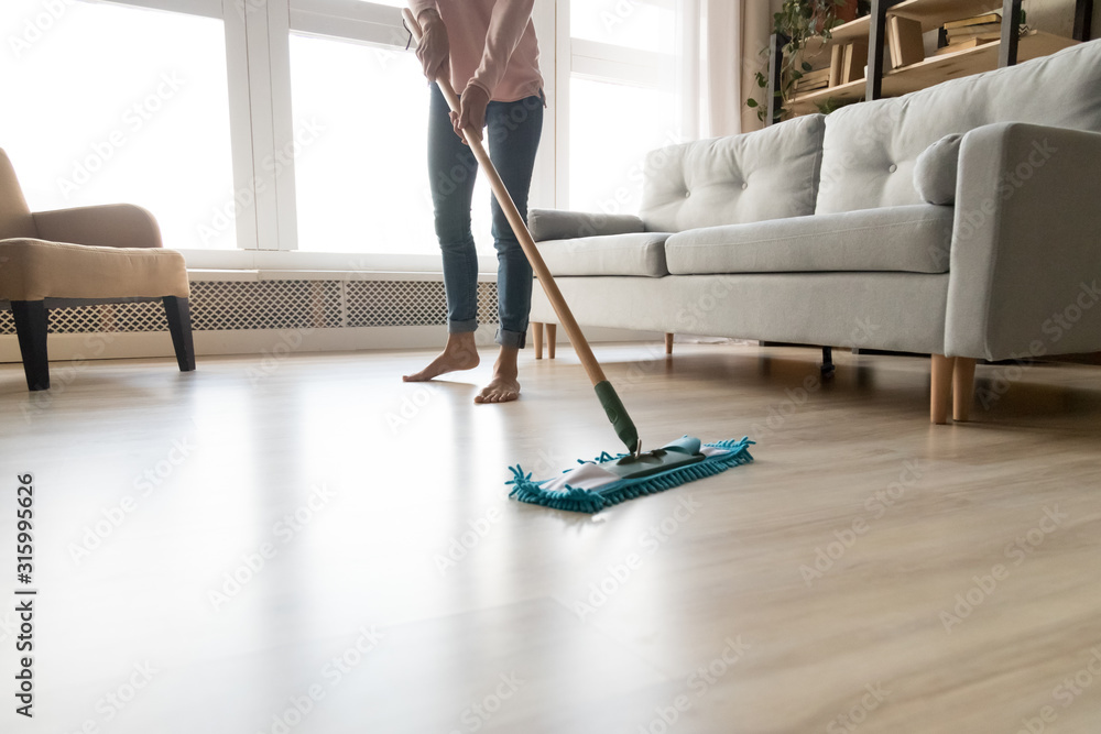 Fototapeta Barefoot woman cleaning floor with wet mop pad cropped image.