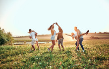 Group Of Happy Young People Dancing On The Field On Beautiful Summer Sunset