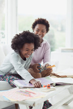 Mother And Daughter Working On Scrapbooking Together