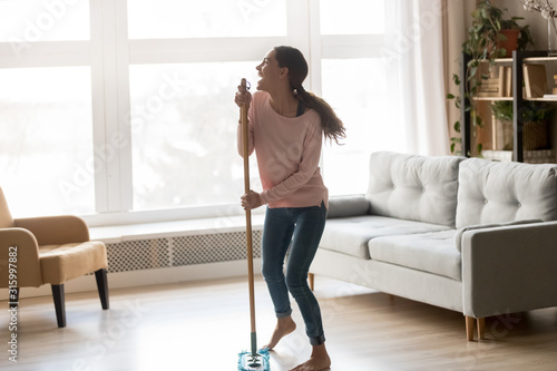 Barefoot young woman singing using microfiber wet mop pad. Wallpaper Mural