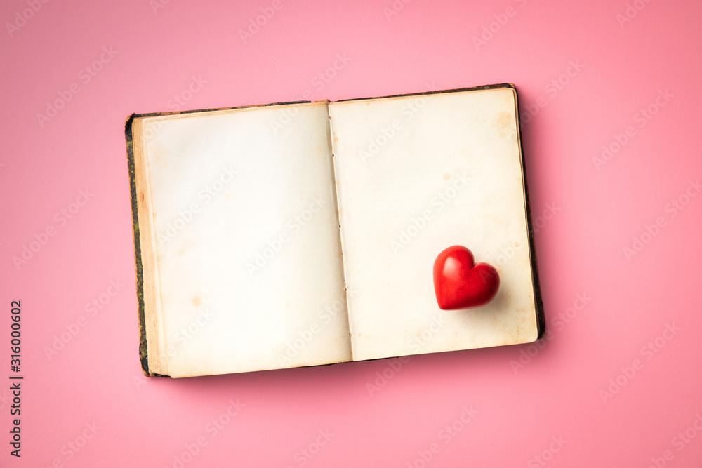 Fototapeta Love concept. Heart on open vintage book.