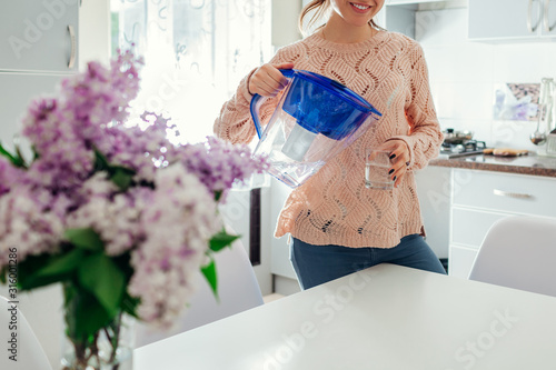 Obraz Woman pouring filtered water from filter jug into glass on kitchen. Modern kitchen design. Healthy lifestyle - fototapety do salonu