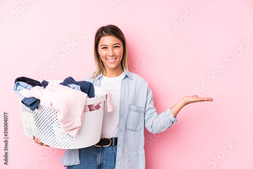 Fototapeta Young caucasian woman picking up a dirty clothes showing a copy space on a palm and holding another hand on waist. obraz
