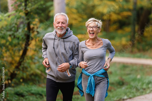 Foto Cheerful active senior couple jogging in the park