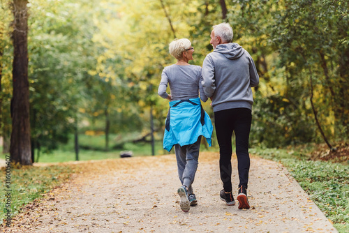 Fototapeta Cheerful active senior couple jogging in the park