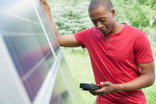 Mid-adult Man Checking Solar Panel With Volt Meter