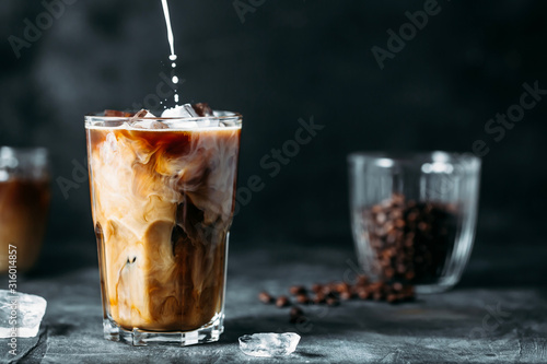 Tableau sur Toile Milk Being Poured Into Iced Coffee on a dark table