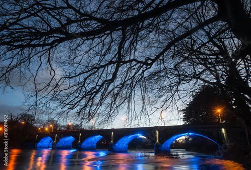 Obraz Old stone bridge illuminated up at night in the town of Listowel, County Kerry, Ireland - fototapety do salonu