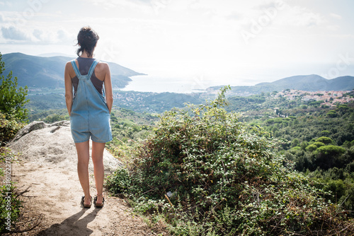 Young woman admiring panorama from hill overseeing bay in Tuscany wearing denim Canvas Print