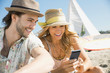 Couple using smart phone together on beach