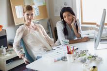 Portrait Of Confident Female Artists At Desk