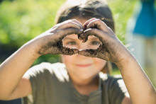 Little Girl Making Heart Shape With Dirt Covered Hands