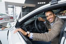 Smiling Man Inside Car In Car Dealership Showroom