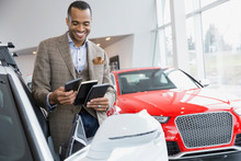 Man Looking At Color Swatches In Car Dealership