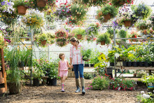 Mother And Daughter Shopping In Plant Nursery Greenhouse
