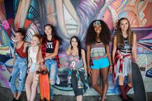 Portrait Of Teenage Girls Leaning Against Graffiti Wall