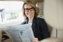 Portrait Of Businesswoman With Newspaper Sitting In Car
