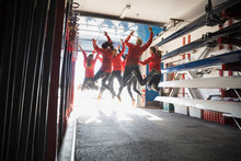 Rowing Team Jumping For Joy In Boathouse
