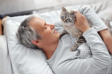 Senior Man Huggin Cat In The Bed