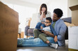 Moving boxes surrounding family using digital tablet