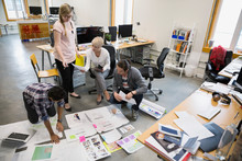 Graphic Designers Meeting Reviewing Proofs On Office Floor