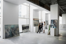 Art Dealers Examining Painting In Art Gallery