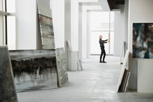 Art Dealer Examining Painting In Art Gallery