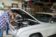 Father And Son Restoring Vintage Car Engine Garage