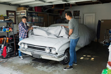 Father And Son Uncovering Vintage Car In Garage