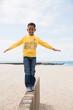 Smiling boy balancing on beach wall