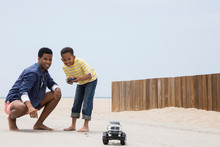 Father And Son Playing Remote Control Truck Beach