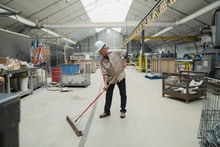 Worker Sweeping In Manufacturing Plant