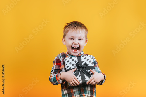 Photo Little boy in shirt holding black and white present for girl or mother, Valentines day, mother's day, Happy surpeised and cute child higging his gift