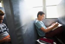 Schoolboy Doing Homework On School Bus