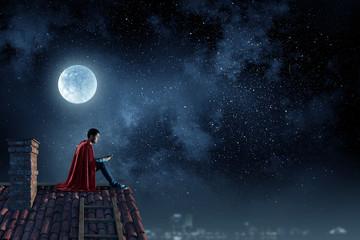 Fototapeta na wymiar Super hero on roof. Mixed media