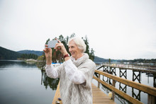 Senior Woman Taking Selfie On Lake Dock