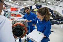Female Helicopter Pilot Explaining Part In Airplane Hangar