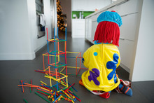Boy In Clown Costume Playing With Connector Sticks