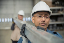 Workers Carrying Steel Beam In Manufacturing Plant