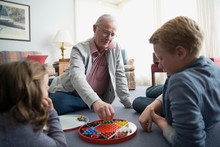Grandfather And Grandchildren Playing Chinese Checkers