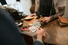 Customer Paying With British Pounds In Leather Shop