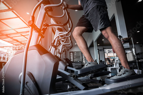Young man working out on an elliptical trainer in gym Wallpaper Mural