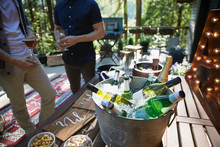 Bottled Beer, Wine And Water On Ice In Bucket At Party