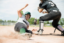 Middle School Girl Softball Player Sliding Into Home Base Next To Catcher