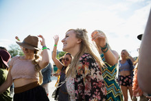 Young Women Dancing In Crowd At Summer Music Festival