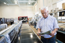 Senior Man With Sale Ad Shopping For Stove In Appliance Store