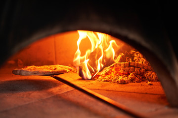 Baked tasty margherita pizza in Traditional wood oven in Naples restaurant, I...