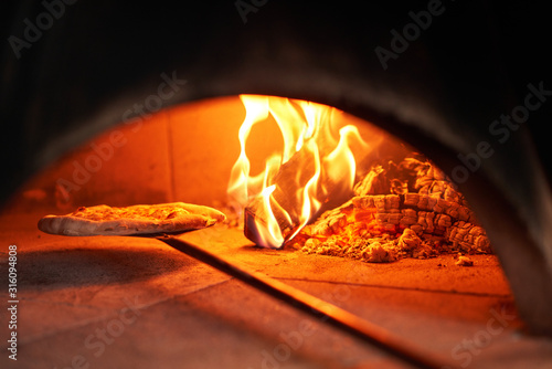 Baked tasty margherita pizza in Traditional wood oven in Naples restaurant, Italy Fototapeta
