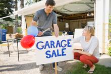 Couple Putting Up Garage Sale ...